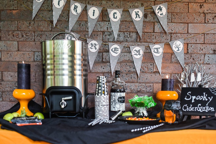 Up Your Trick or Treating Game with a Spooky Front Porch Cider Station
